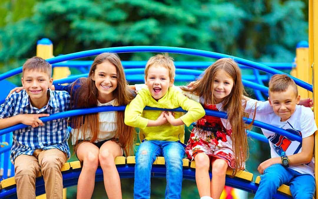 five kids sitting on daycare playground equipment
